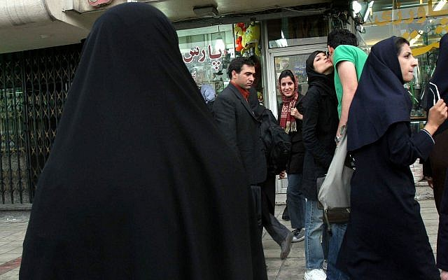 FILE -- An Iranian policewoman, left, (back to camera) watches as two Iranian friends kiss before restraining them on a street in Tehran, Iran Saturday April 22, 2006. (AP Photo/STR)