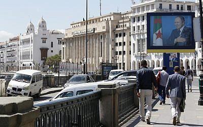 Illustrative: Algerians walk past a portrait of Algerian President Abdelaziz Bouteflika in the capital Algiers on May 2, 2017. (AP Photo/Toufik Doudou)