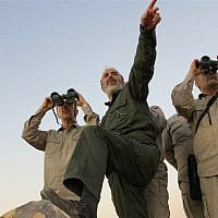 This file photo provided on Friday Oct. 20, 2017 by the government-controlled Syrian Central Military Media, shows Iran's army chief of staff Maj. Gen. Mohammad Bagheri, left, looks into binoculars as he visits and other senior officers from the Iranian military a front line in the northern province of Aleppo, Syria.  (Syrian Central Military Media, via AP)