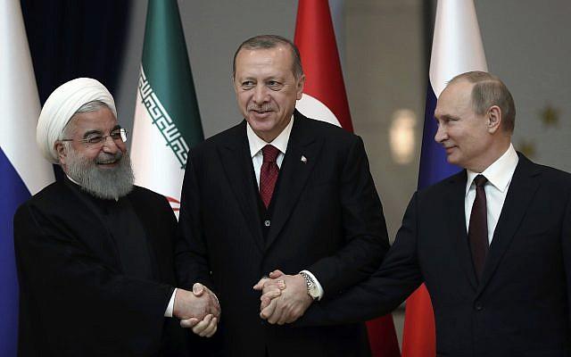 Iran's President Hassan Rouhani, left, Russia's President Vladimir Putin, right, and Turkey's President Recep Tayyip Erdogan lock hands during a group photo in Ankara, Turkey, April 4, 2018. (Tolga Bozoglu/Pool Photo via AP)