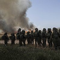 Illustrative: Israeli soldiers watch a wheat field that caught fire next to kibbutz Nahal Oz along the Israel-Gaza border, May 14, 2018 (AP Photo/Tsafrir Abayov)