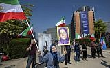 Supporters of the National Council of Resistance of Iran wave flags and hold a photo of Maryam Rajavi, leader of the People's Mujahedin of Iran, outside of a meeting of Iranian Foreign Minister Javad Zarif and European Union foreign policy chief Federica Mogherini at the Europa building in Brussels on Tuesday, May 15, 2018. (AP Photo/Olivier Matthys)