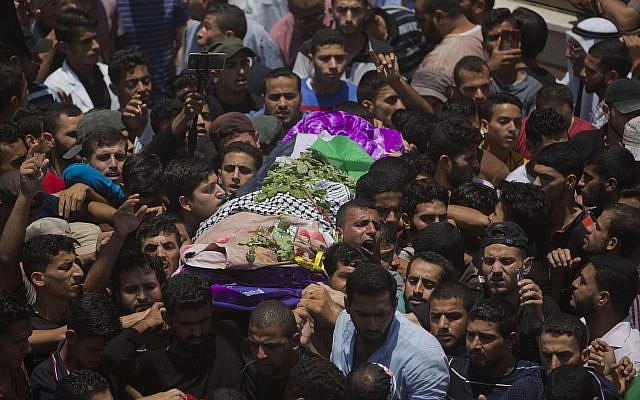 FILE - In this Saturday, June 2, 2018 file photo, Palestinian mourners carry the body of volunteer paramedic Razan Najjar, 21, during her funeral in town of Khan Younis, Southern Gaza Strip (AP Photo/Khalil Hamra, File)