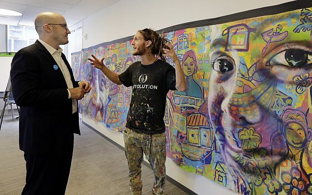 In this June 20, 2018, photo, vice president of marketing and communications for UNICEF USA Francesco De Flaviis, left, talks with co-founder and co-director of Artolution, Max Levi Frieder, of Denver, beside a mural created by Rohingya refugees that's displayed at the offices of UNICEF USA, in New York. (AP Photo/Richard Drew)