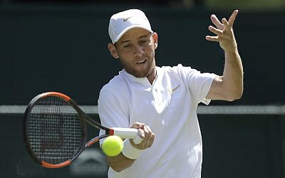 Dudi Sela of Israel returns the ball to Spaniard Rafael Nadal during their men's singles match, on the second day of the Wimbledon Tennis Championships in London, July 3, 2018. (AP Photo/Ben Curtis)