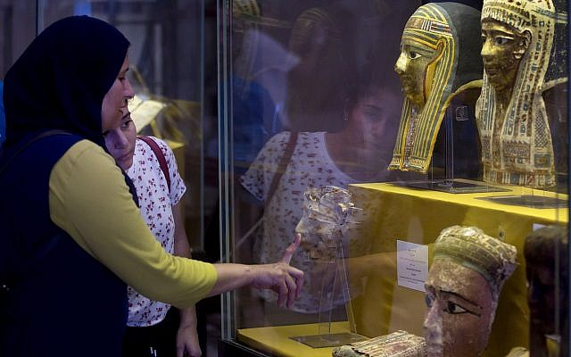 Reporters film recently discovered gilded mummy mask found in a disturbed context of the hall way of a burial chamber dating back some 2,500 years at an ancient necropolis near Egypt's famed pyramids in Saqqara, Giza, Saturday, July 14, 2018. (AP/Amr Nabil)