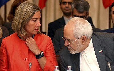 European Union High Representative for Foreign Affairs Federica Mogherini and Iranian Foreign Minister Mohammad Javad Zarif, from left, wait for the start of prior to a bilateral meeting as part of the closed-door nuclear talks with Iran at a hotel in Vienna, Austria, on July 6, 2018. (AP Photo/Ronald Zak)