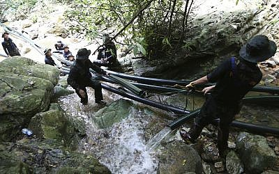 Thai soldiers drag water pipes used to pump water out a cave complex where 12 boys and their soccer coach are trapped in northern Thailand, July 7, 2018 (AP Photo/Sakchai Lalit)