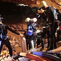 In this undated photo released by Royal Thai Navy on Saturday, July 7, 2018, Thai rescue team members walk inside a cave where 12 boys and their soccer coach have been trapped since June 23, in Mae Sai, Chiang Rai province, northern Thailand (Royal Thai Navy via AP)