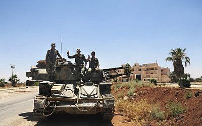 Syrian soldiers flashing the victory sign as they sit on their military vehicle at Naseeb border crossing with Jordan, in the southern province of Daraa, Syria, July 7, 2018. (SANA via AP)