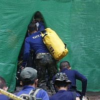 Rescuers arrive near the cave where 12 boys and their soccer coach have been trapped since June 23, in Mae Sai, Chiang Rai province, in northern Thailand Sunday, July 8, 2018. (AP Photo/Sakchai Lalit)