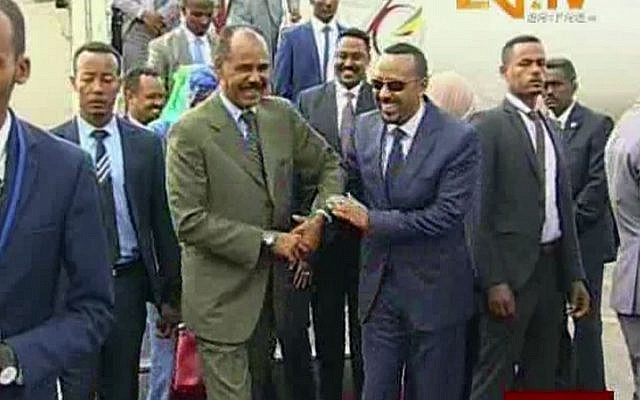 In this grab taken from video provided by ERITV, Ethiopia's Prime Minister Abiy Ahmed, center right, is welcomed by Erirea's President Isaias Afwerki as he disembarks the plane, in Asmara, Eritrea, July 8, 2018. (ERITV via AP)