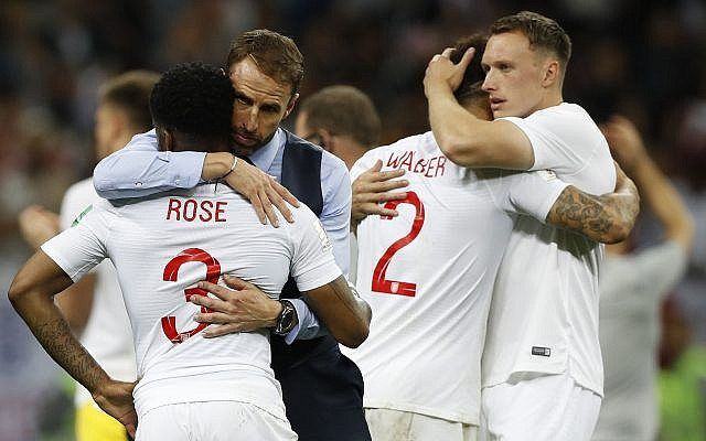 England head coach Gareth Southgate, 2nd left, comforts England's Danny Rose, left, after losing the semifinal match between Croatia and England at the 2018 World Cup in the Luzhniki Stadium in Moscow, Russia, Wednesday, July 11, 2018. (AP Photo/Francisco Seco)