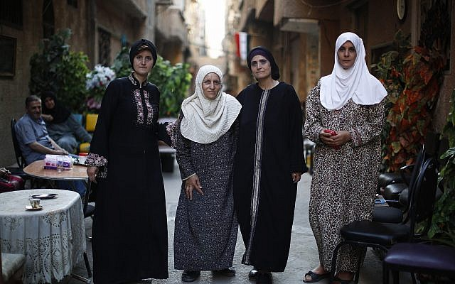 In this July 16, 2018 photo, Palestinian Abdul-Mahmoud sisters from right to left, Amal, Hanan, Izdihar, Myasar, pose for a picture outside their house on Lod street at the Palestinian refugee camp of Yarmouk in the Syrian capital Damascus, Syria. (AP Photo/Hassan Ammar)