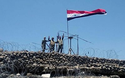 In this Tuesday, July 17, 2018, photo, released by the Syrian official news agency SANA, Syrian troops flash the victory sign next to the Syrian flag in Tell al-Haara, the highest hill in the southwestern Daraa province, Syria. (SANA via AP)