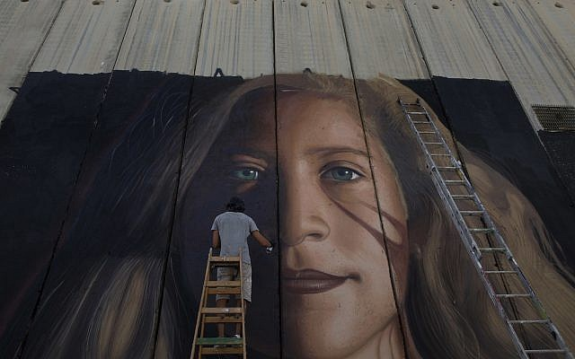 An artist paints a giant mural of prominent Palestinian activist Ahed Tamimi on part of the Israeli security barrier, in the West Bank city of Bethlehem on July 25, 2018. (AP Photo/Nasser Nasser)