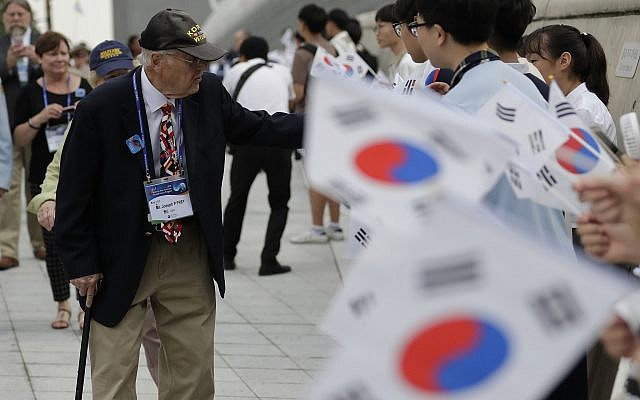 U.S. veteran of the Korean War Joseph P. Frey, left, is welcomed by South Korean students waving South Korean national flags upon veterans arrival to attend the commemorating ceremony for the U.N. Force Participating Day in the Korean War in Seoul, South Korea, Friday, July 27, 2018. (AP/Lee Jin-man)