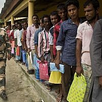 Muslims stand in a queue to check if their names are included in the National Register of Citizens at a draft center in Bur Gaon village, 70 kilometers (44 miles) east of Gauhati, India, July 30, 2018. (AP Photo/Anupam Nath)