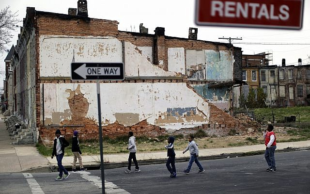In this April 4, 2013 file photo, a group of boys walk past a partially collapsed row house in Baltimore. (AP/Patrick Semansky)