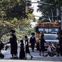 Illustrative: Children and adults cross a street in front of a school bus in Borough Park, a neighborhood in the Brooklyn borough of New York that is home to many ultra-Orthodox Jewish families. (AP/Bebeto Matthews)
