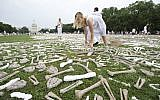 Jess Perkins from Napier, New Zealand, places bones, crafted by students, artists and activists, on the lawn of the National Mall Washington as part of a visible petition for bold action towards an end to genocide and mass atrocities, Saturday, June 8, 2013. (AP/Manuel Balce Ceneta)