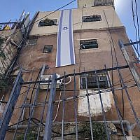 The Israeli flag is mounted on a building owned by Ateret Cohanim in the Batan al-Hawa neigbhorhood of Silwan, East Jerusalem, July 31, 2018. (Sue Surkes)