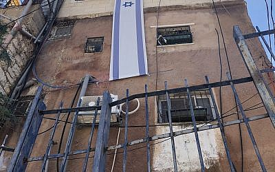 The Israeli flag is mounted on a building owned by Ateret Cohanim in the Batan al-Hawa neigbhorhood of Silwan, East Jerusalem, July 31, 2018. (Sue Surkes)