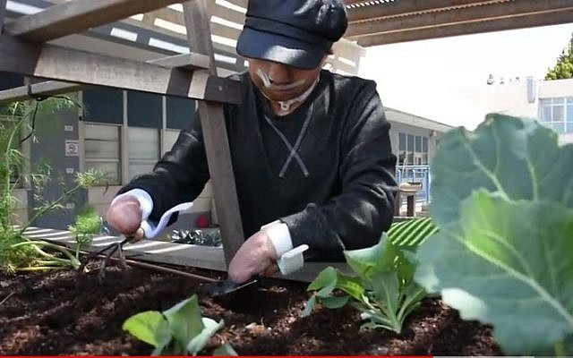 Thala works in the garden with the devices created by Alyn hospital in Jerusalem to help her hold on to the tools (YouTube screen shot)