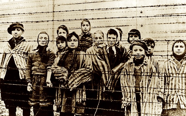 A group of children wearing concentration camp uniforms behind barbed wire fencing in the Oswiecim (Auschwitz) Nazi concentration camp, photographed just after the liberation by the Soviet army, in January 1945. (AP Photo/ File)