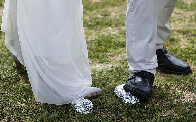 The legs of bride Lin Dror (L) and groom Alon Marcus (R) are seen as they break two glasses concluding their Reform Jewish wedding ceremony held in front of the Knesset, in Jerusalem, on March 18, 2013, in protest of the Orthodox Rabbinate's monopoly on marriage licensing and the lack of civil marriages in Israel. (Flash 90)
