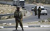 Illustrative: Israeli soldiers block the entrance to the industrial zone of the southern West Bank city of Hebron, on June 15, 2014. (Hadas Parush/Flash90/File)