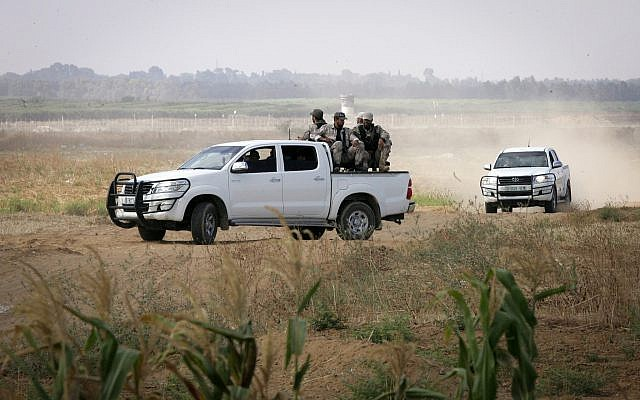 Illustrative: Members of the Hamas terror group's armed wing sit in the back of a pick-up truck watching Israeli bulldozers working along a barbed wire fence that separates Khan Younis in the southern Gaza Strip from Israel, on June 10, 2015. (Abed Rahim Khatib /Flash90)