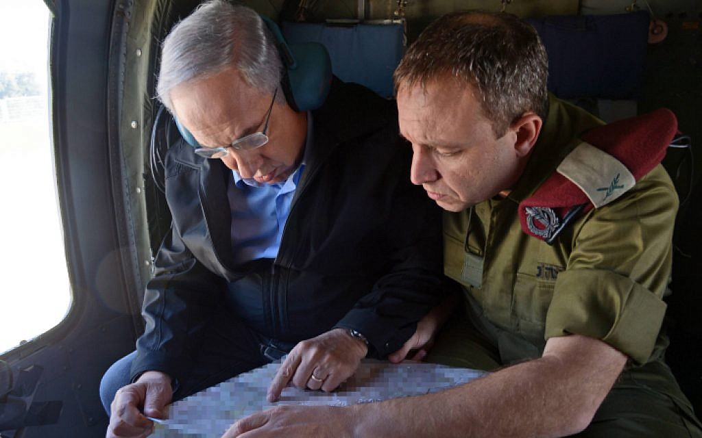 Prime Minister Benjamin Netanyahu, left, speaks with his military secretary, Brig. Gen. Eliezer Toledano, right, on his way to a visit in the Etzion bloc in the West Bank on November 23, 2015, following a spate of terror attacks in the area. (Haim Zach/GPO)