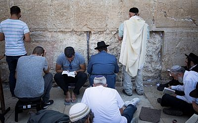 Illustrative: Jewish men pray at the Western Wall in the Old City of Jerusalem during the Tisha B'Av fast marking the destruction of the Temples, on August 1, 2017. (Yonatan Sindel/Flash90)