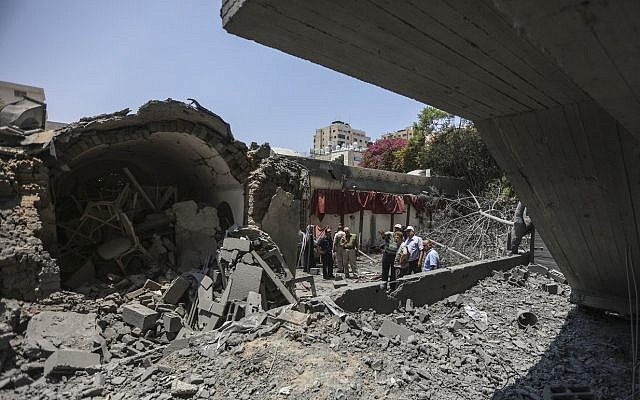 Palestinians walk through the wreckage of a building that was damaged by Israeli air strikes in Gaza City on July 15, 2018 (Wissam Nassar/Flash90)