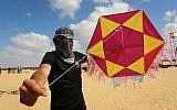 File: Palestinian protestors fly a kite loaded with an incendiary device towards Israel during a demonstration along the border with Israel east of Rafah in the southern Gaza Strip, on June 29, 2018 (Abed Rahim Khatib/Flash90)