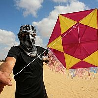A Palestinian protester displays a kite loaded with an incendiary device before launching it towards Israel, east of Rafah in the southern Gaza Strip, on June 29, 2018 (Abed Rahim Khatib/Flash90)