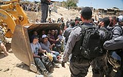 Israeli policemen scuffle with Palestinian demonstrators in the Bedouin village of Khan al-Ahmar, east of Jerusalem, on July 4, 2018. (FLASH90)