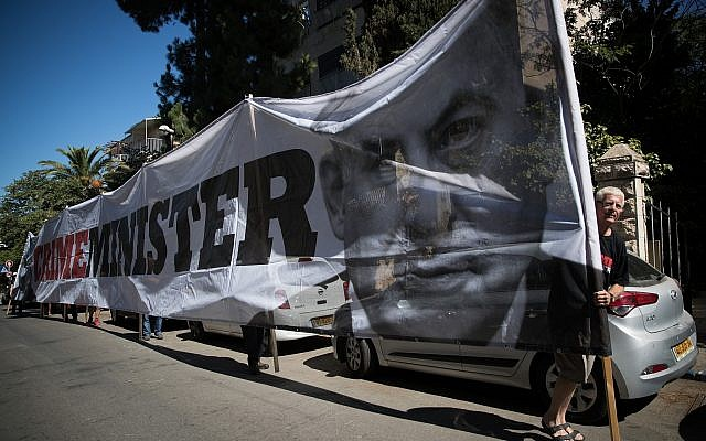 """Protesters outside the Prime Minister's Residence hold a sign reading """"Crime Minister,' as police investigators arrive to question Benjamin Netanyahu, July 10, 2018.(Yonatan Sindel/Flash90)"""