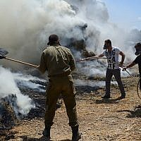 Israeli firefighters and security teams fight a fire at and around a cowshed, caused by a kite loaded with an incendiary device from Gaza, at Kibbutz Nahal-Oz on July 21, 2018. (Gili Yaari/FLASH90)