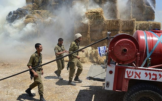 Firefighters and security teams fight a fire at a cowshed, caused by a kite loaded with an incendiary device from Gaza, at Kibbutz Nahal-Oz on July 21, 2018. (Gili Yaari/FLASH90)