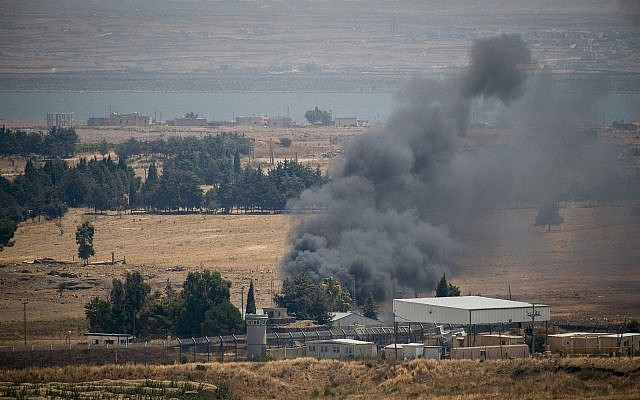 Smoke rises from Quneitra, at the Syrian side of the Israeli-Syrian border in the Golan Heights, on July 22, 2018. (Basel Awidat/Flash90)