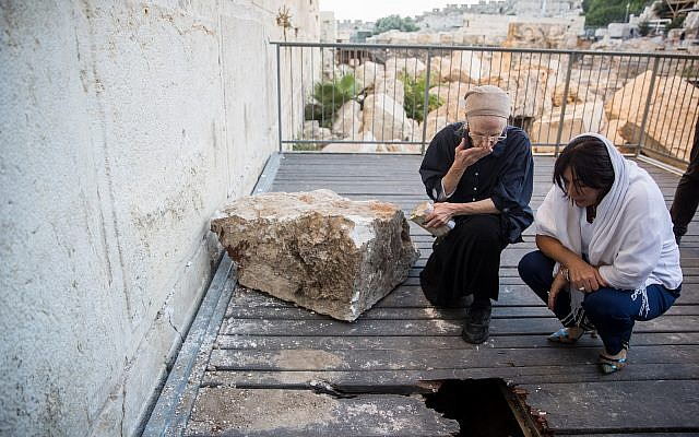 Daniella Goldberg (left), with Culture Minister Miri Regev, inspects the damage caused by a large stone that dislodged from the Western Wall in Jerusalem Old City on July 23, 2013, at the mixed-gender prayer section. The boulder fell close to where Goldberg was praying. (Yonatan Sindel/Flash90)