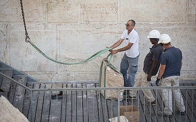 Workers attach a crane to a large chunk of stone dislodged from the Western Wall in Jerusalem Old City, at the mixed-gender prayer section, July 25, 2018. (Hadas Parush/Flash90)