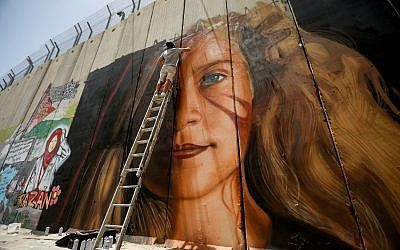 A man paints a mural of Palestinian Ahed Tamimi on a part of Israel's West Bank security barrier in the West Bank city of Bethlehem, July 25, 2018. (Wisam Hashlamoun/Flash90)