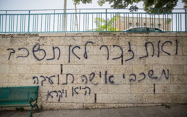 """Hebrew graffiti reading """"Thou shalt not lie with mankind, as with womankind: It is abomination -- Leviticus,"""" is seen spray painted on a wall in Jerusalem on July 25, 2018, near where 16-year-old was stabbed to death by an ultra-Orthodox extremist during the 2015 gay pride parade in the city. (Yonatan Sindel/Flash90)"""