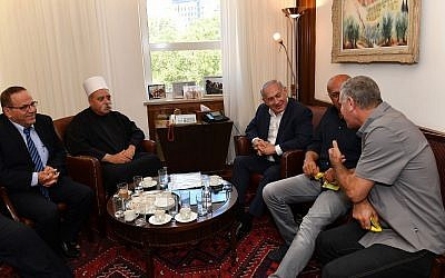 Prime Minister Benjamin Netanyahu (C) meets with Sheikh Muafak Tariff, spiritual leader of Israel's Druze community, Communications Minister Ayoub Kara (L) and other Druze leaders at his office in Jerusalem to discuss the nation-state law on July 27, 2018. (Kobi Gideon/GPO/Flash90)
