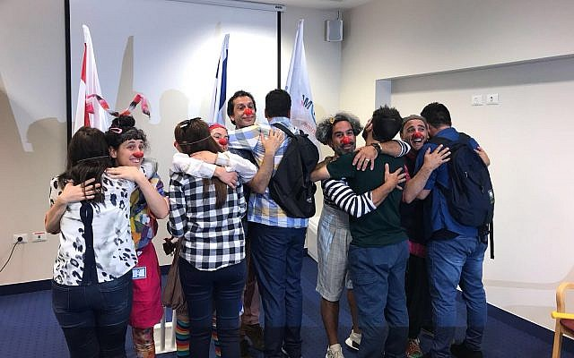 A group of Yazidis from Iraq (with their backs to the camera) together with Israeli trainers who gave them a course on medical clowning, June 2018. (Israel's Foreign Ministry)