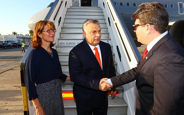 Minister Ofir Akunis, right, greets Viktor Orban, center, and his wife Aniko Levai at Ben-Gurion Airport on July 18, 2018. (Foreign Ministry)