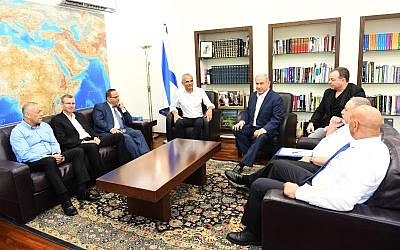 Prime Minister Benjamin Netanyahu (center-right) meets with Finance Minister Moshe Kahlon (center-left), Communications Minister Ayoub Kara (3rd-left), Tourism Minister Yariv Levin (2nd-left), Kulanu MK Akram Hasson (left), Yisrael Beytenu MK Hamad Amar (right), Defense Minister Avigdor Liberman (2nd-right) and his chief of staff Yoav Horowitz (3rd-right) on July 26, 2018. (Haim Tzach/GPO)